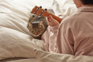 ウクレレを弾く女性と猫の写真素材 [FYI04728879]