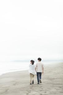 海辺を歩くカップルの後ろ姿の写真素材 [FYI04728880]