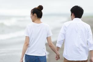 海辺を歩くカップルの後ろ姿の写真素材 [FYI04728888]
