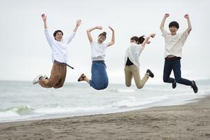 海辺でジャンプする若者の写真素材 [FYI04728893]