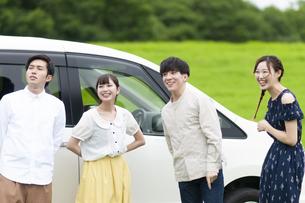 車の側で微笑む若者の写真素材 [FYI04728903]