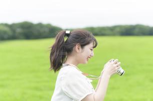 草原でカメラを持つ女性の写真素材 [FYI04728913]