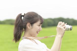 草原でカメラを持つ女性の写真素材 [FYI04728915]