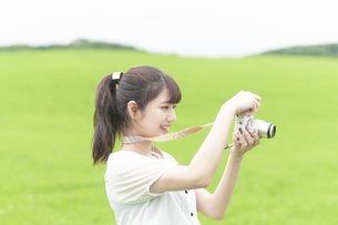 草原でカメラを持つ女性の写真素材 [FYI04728917]