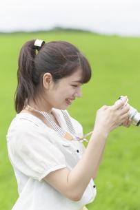 草原でカメラを持つ女性の写真素材 [FYI04728926]