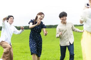 草原で写真を撮る若者の写真素材 [FYI04728929]
