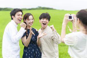 草原で写真を撮る若者の写真素材 [FYI04728930]
