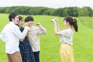 草原で写真を撮る若者の写真素材 [FYI04728931]