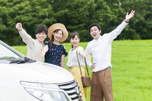 車の側でポーズをとる若者の写真素材 [FYI04728934]