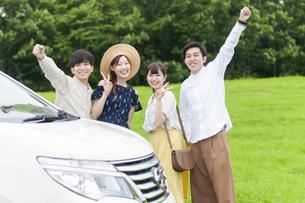 車の側でポーズをとる若者の写真素材 [FYI04728935]