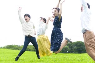 草原で跳ぶ若者の写真素材 [FYI04728948]