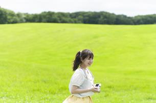 草原でカメラを持つ女性の写真素材 [FYI04728957]