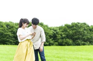 草原でスマホを見るカップルの写真素材 [FYI04728972]