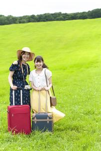 草原の中でスーツケースを持つ若い女性達の写真素材 [FYI04728979]