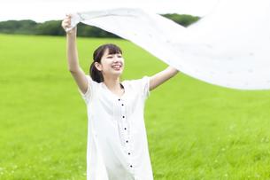 草原で布を広げる若い女性の写真素材 [FYI04728983]