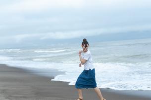 海辺で走る若い女性の写真素材 [FYI04728991]