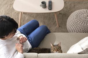 ソファでくつろぐ猫と女性の写真素材 [FYI04728995]