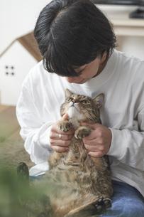 膝の上に座る猫と女性の写真素材 [FYI04729014]