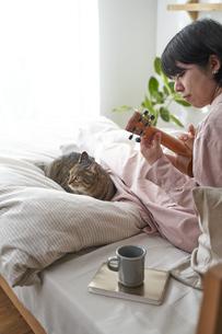 ベッドの上でウクレレを弾く女性と猫の写真素材 [FYI04729028]