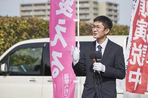 選挙活動をするスーツを着た男性の写真素材 [FYI04729090]