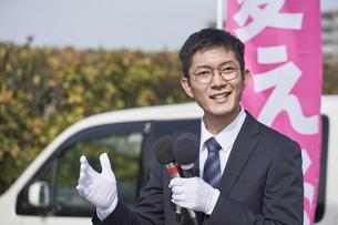選挙活動をするスーツを着た男性の写真素材 [FYI04729095]