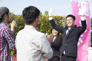 選挙活動をするスーツを着た男性の写真素材 [FYI04729110]