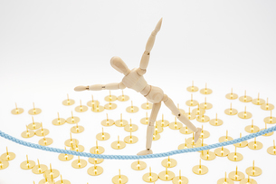 画鋲が撒かれた地面の上でよろけながら綱渡りをするデッサン人形の写真素材 [FYI04729116]