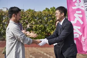 選挙活動をするスーツを着た男性の写真素材 [FYI04729122]