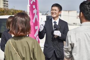 選挙活動をするスーツを着た男性の写真素材 [FYI04729126]