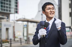 街中で演説をするスーツを着た男性の写真素材 [FYI04729157]