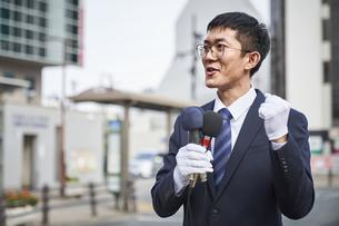 街中で演説をするスーツを着た男性の写真素材 [FYI04729158]