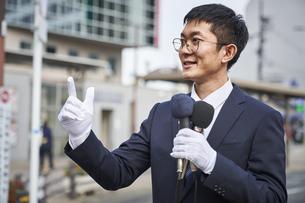 街中で演説をするスーツを着た男性の写真素材 [FYI04729164]