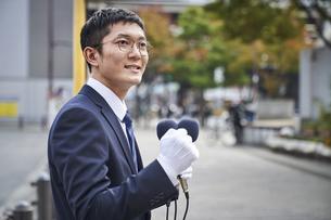 街中で演説をするスーツを着た男性の写真素材 [FYI04729166]