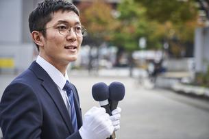 街中で演説をするスーツを着た男性の写真素材 [FYI04729168]