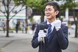 街中で演説をするスーツを着た男性の写真素材 [FYI04729169]