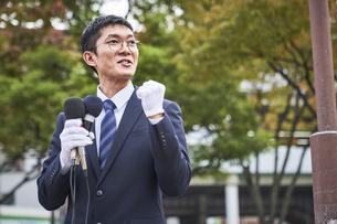 街中で演説をするスーツを着た男性の写真素材 [FYI04729170]