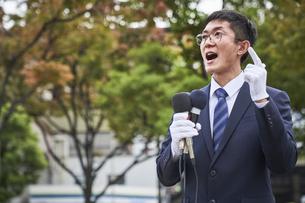街中で演説をするスーツを着た男性の写真素材 [FYI04729171]