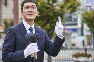 街中で演説をするスーツを着た男性の写真素材 [FYI04729172]