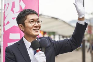 街中で選挙活動をするスーツを着た男性の写真素材 [FYI04729177]