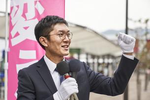 街中で選挙活動をするスーツを着た男性の写真素材 [FYI04729178]