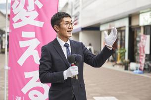 街中で選挙活動をするスーツを着た男性の写真素材 [FYI04729180]