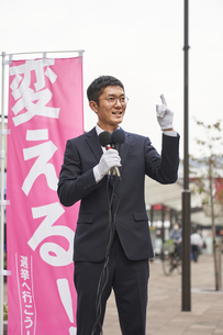 街中で選挙活動をするスーツを着た男性の写真素材 [FYI04729181]