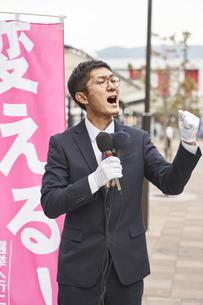 街中で選挙活動をするスーツを着た男性の写真素材 [FYI04729182]