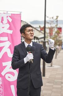 街中で選挙活動をするスーツを着た男性の写真素材 [FYI04729184]