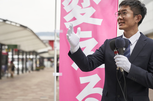 街中で選挙活動をするスーツを着た男性の写真素材 [FYI04729185]