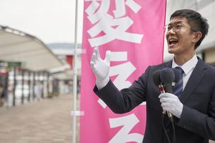 街中で選挙活動をするスーツを着た男性の写真素材 [FYI04729186]