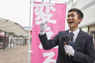 街中で選挙活動をするスーツを着た男性の写真素材 [FYI04729188]