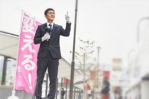 街中で選挙活動をするスーツを着た男性の写真素材 [FYI04729190]