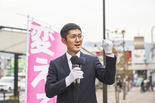 街中で選挙活動をするスーツを着た男性の写真素材 [FYI04729192]