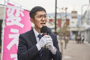 街中で選挙活動をするスーツを着た男性の写真素材 [FYI04729193]